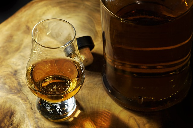 Et flot whiskeyglas med whiskey i står på et bordbord